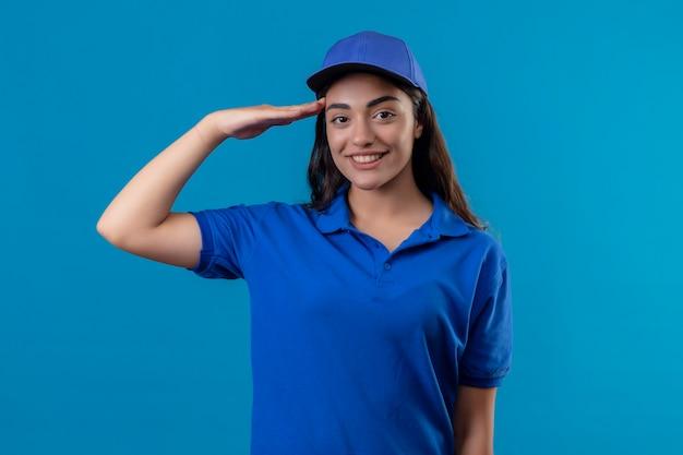 Jovem entregadora de uniforme azul e boné saudando olhando para a câmera com um sorriso confiante no rosto em pé sobre um fundo azul