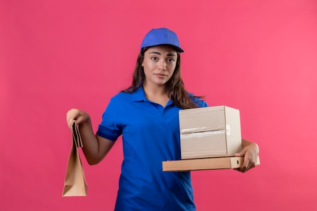 Jovem entregadora de uniforme azul e boné segurando caixas de papelão e um pacote de papel parecendo infeliz em pé com uma expressão triste no rosto sobre fundo rosa