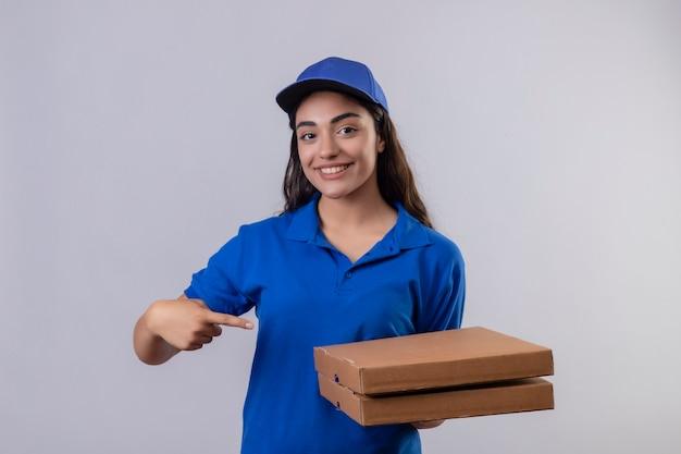 Jovem entregadora de uniforme azul e boné segurando caixas de pizza apontando com o dedo para elas sorrindo confiante em pé sobre um fundo branco