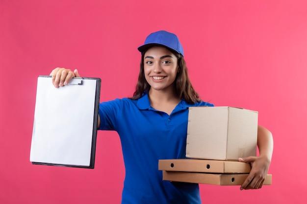 Jovem entregadora de uniforme azul e boné segurando caixas de pizza e embalagem mostrando a prancheta olhando para a câmera sorrindo amigável em pé sobre fundo rosa