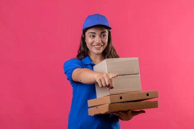 Jovem entregadora de uniforme azul e boné segurando caixas de pizza e pacote de caixa olhando para o lado apontando com o dedo para algo sorridente amigável em pé sobre fundo rosa