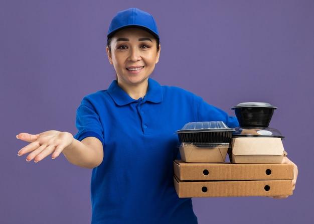 Jovem entregadora de uniforme azul e boné segurando caixas de pizza e pacotes de comida com o braço estendido sorrindo alegremente em pé sobre a parede roxa