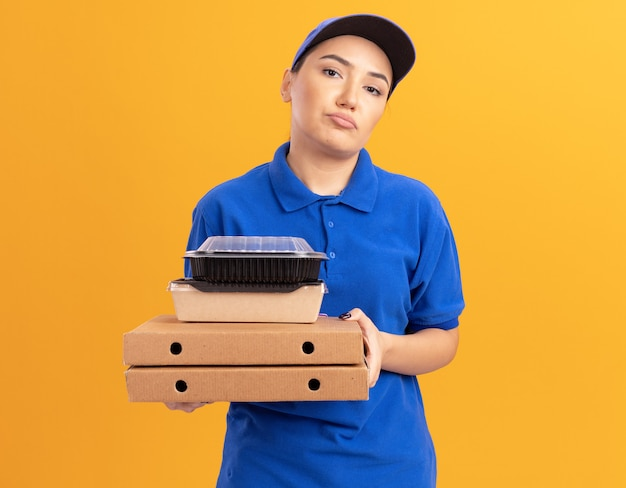 Jovem entregadora de uniforme azul e boné segurando caixas de pizza e pacotes de comida olhando para a frente com uma expressão triste no rosto em pé sobre a parede laranja