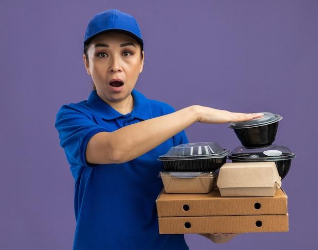 Jovem entregadora de uniforme azul e boné segurando caixas de pizza e pacotes de comida pasma e surpresa em pé sobre a parede roxa