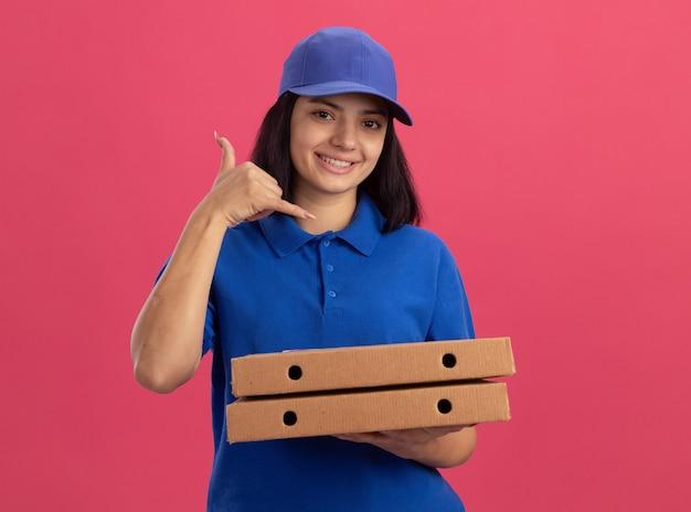 Jovem entregadora de uniforme azul e boné segurando caixas de pizza fazendo gesto de me ligar sorrindo em pé sobre a parede rosa