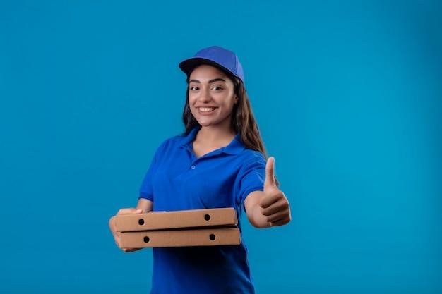 Jovem entregadora de uniforme azul e boné segurando caixas de pizza, olhando para a câmera, sorrindo amigável, feliz e positiva, mostrando os polegares em pé sobre um fundo azul