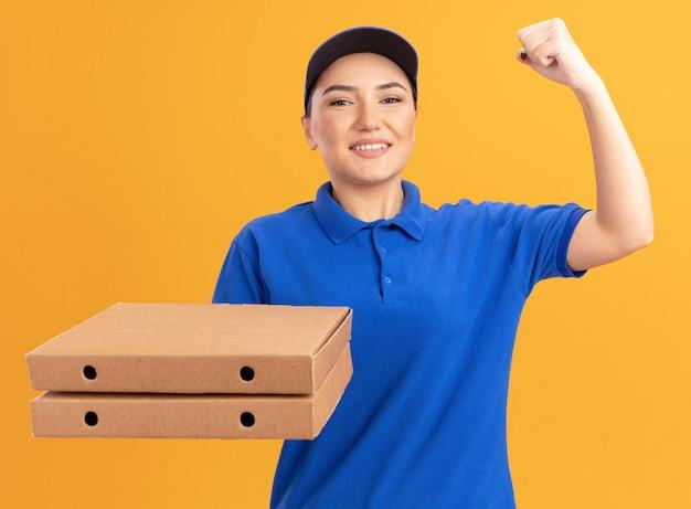 Jovem entregadora de uniforme azul e boné segurando caixas de pizza, olhando para a frente, sorrindo confiante e erguendo o punho como uma vencedora em pé sobre uma parede laranja