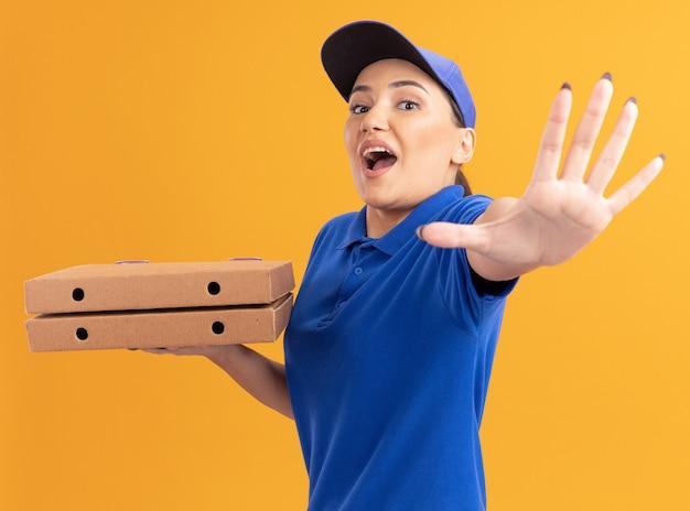 Jovem entregadora de uniforme azul e boné segurando caixas de pizza olhando para frente, fazendo gesto de parada com a mão preocupada em pé sobre a parede laranja