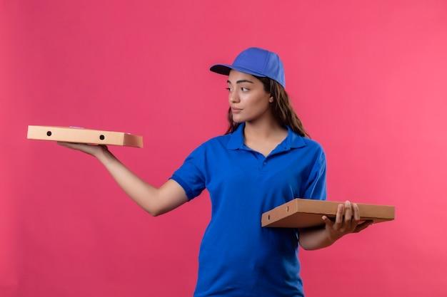 Jovem entregadora de uniforme azul e boné segurando caixas de pizza olhando para o lado com uma expressão facial confiante e séria em pé sobre um fundo rosa