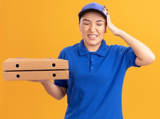 Jovem entregadora de uniforme azul e boné segurando caixas de pizza, parecendo confusa com a mão na cabeça por engano em pé sobre a parede laranja