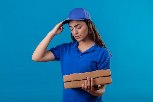 Jovem entregadora de uniforme azul e boné segurando caixas de pizza parecendo indisposta tocando a cabeça e sofrendo de dor de cabeça em pé sobre um fundo azul
