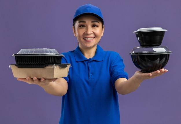 Jovem entregadora de uniforme azul e boné segurando pacotes de comida, sorrindo alegremente em pé sobre a parede roxa