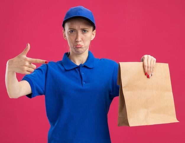 Jovem entregadora de uniforme azul e boné segurando um pacote de papel apontando com o dedo indicador para ele com uma expressão triste franzindo os lábios em pé sobre a parede rosa