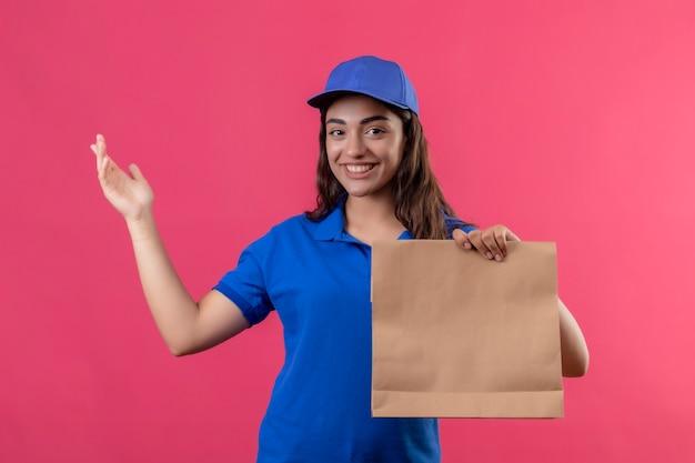 Jovem entregadora de uniforme azul e boné segurando um pacote de papel, apresentando-se com o braço da mão, olhando para a câmera com um sorriso no rosto feliz e positivo em pé sobre um fundo rosa