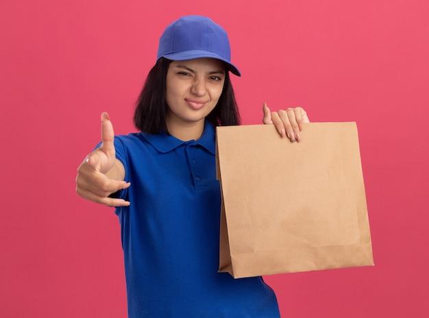 Jovem entregadora de uniforme azul e boné segurando um pacote de papel com um marcador de impressão confiante com o dedo indicador para você em pé sobre a parede rosa