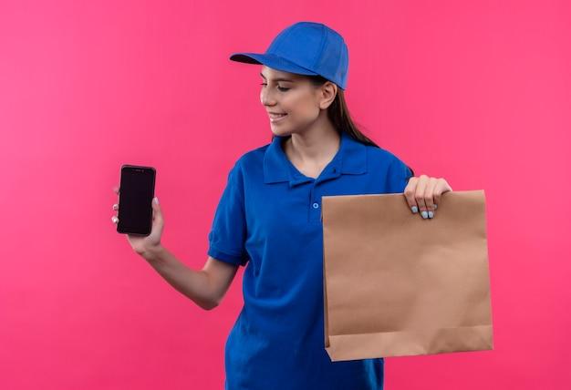 Jovem entregadora de uniforme azul e boné segurando um pacote de papel e smartphone olhando para ele com um sorriso no rosto