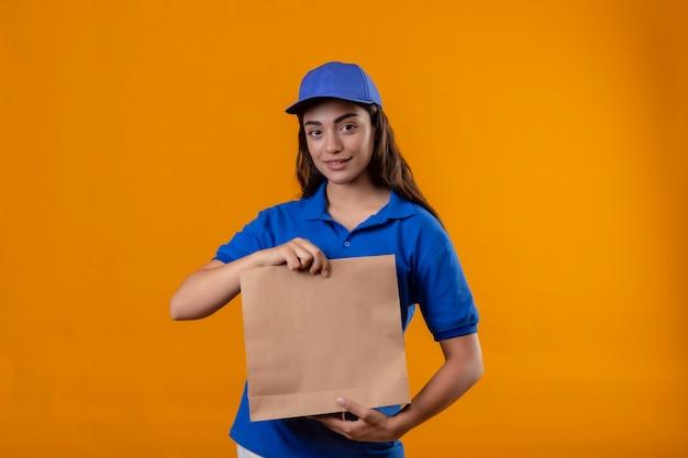 Jovem entregadora de uniforme azul e boné segurando um pacote de papel, olhando para a câmera, sorrindo amigável em pé sobre um fundo amarelo