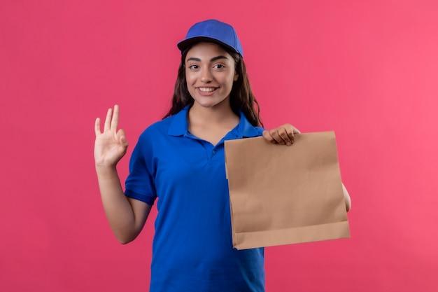 Jovem entregadora de uniforme azul e boné segurando um pacote de papel, olhando para a câmera, sorrindo amigável fazendo sinal de ok em pé sobre fundo rosa