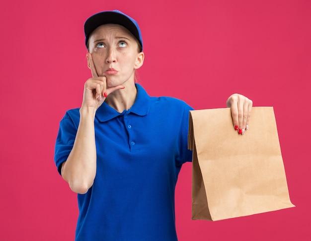 Jovem entregadora de uniforme azul e boné segurando um pacote de papel, olhando para cima confusa em pé sobre a parede rosa