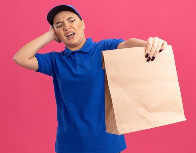 Jovem entregadora de uniforme azul e boné segurando um pacote de papel, olhando para ele com expressão confusa e descontente em pé sobre a parede rosa