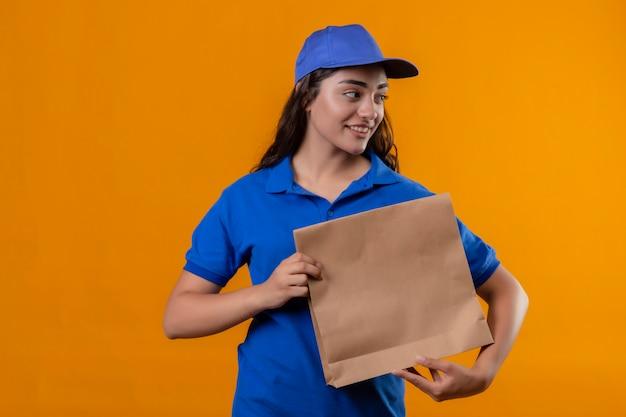 Jovem entregadora de uniforme azul e boné segurando um pacote de papel olhando para o lado e sorrindo amigável em pé sobre um fundo amarelo