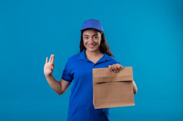 Jovem entregadora de uniforme azul e boné segurando um pacote de papel, sorrindo alegremente fazendo sinal de ok em pé sobre um fundo azul