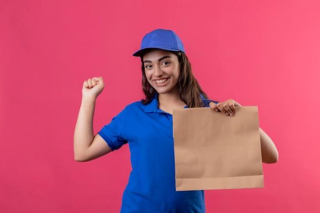 Jovem entregadora de uniforme azul e boné segurando um pacote de papel, sorrindo alegremente, levantando o punho e comemorando seu sucesso e vitória em pé sobre fundo rosa