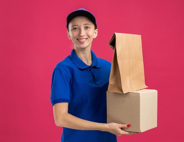 Jovem entregadora de uniforme azul e boné segurando uma caixa de papelão e um pacote de papel olhando para camrera sorrindo confiante em pé sobre a parede rosa