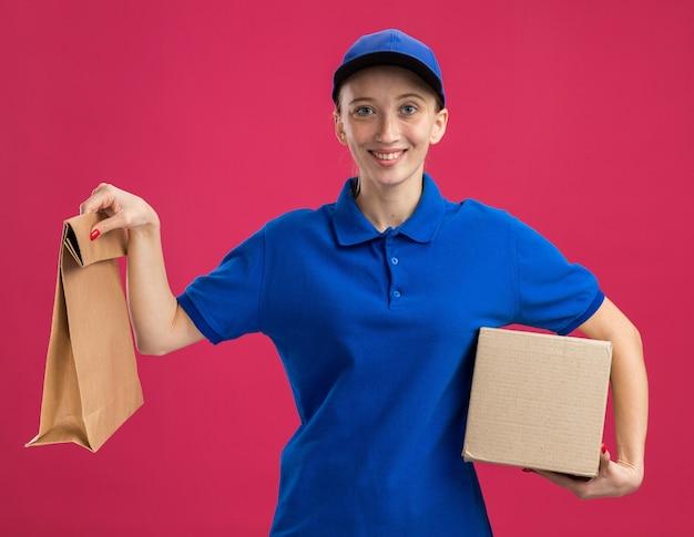 Jovem entregadora de uniforme azul e boné segurando uma caixa de papelão e um pacote de papel sorrindo confiante em pé sobre a parede rosa