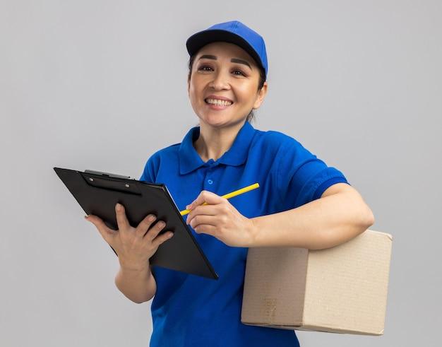 Jovem entregadora de uniforme azul e boné segurando uma caixa de papelão e uma prancheta escrevendo algo sorridente e confiante em pé sobre uma parede branca