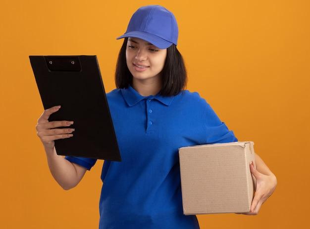 Jovem entregadora de uniforme azul e boné segurando uma caixa de papelão e uma prancheta olhando para ela com um sorriso no rosto em pé sobre a parede laranja