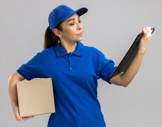 Jovem entregadora de uniforme azul e boné segurando uma caixa de papelão e uma prancheta olhando para ela com uma cara séria em pé sobre uma parede branca