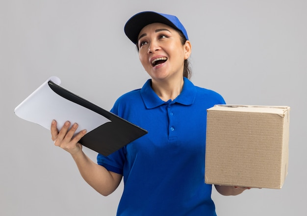 Jovem entregadora de uniforme azul e boné segurando uma caixa de papelão e uma prancheta olhando para o lado e sorrindo alegremente em pé sobre uma parede branca