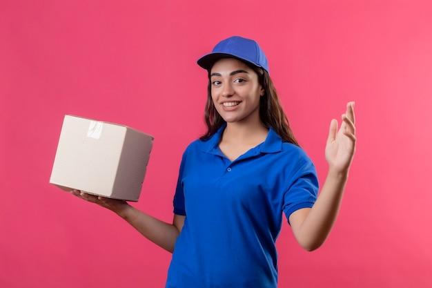 Jovem entregadora de uniforme azul e boné segurando uma caixa de papelão, levantando a mão, olhando para a câmera com um sorriso no rosto feliz e positivo em pé sobre um fundo rosa
