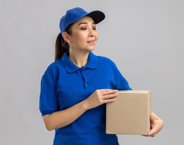 Jovem entregadora de uniforme azul e boné segurando uma caixa de papelão olhando para o lado com expressão confiante em pé sobre uma parede branca
