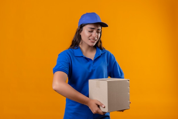 Jovem entregadora de uniforme azul e boné segurando uma caixa de papelão, parecendo um pneu e entediada em pé sobre um fundo amarelo