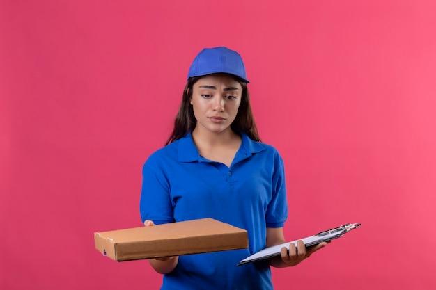 Jovem entregadora de uniforme azul e boné segurando uma caixa de pizza e uma prancheta em pé com uma expressão triste no rosto em pé sobre um fundo rosa