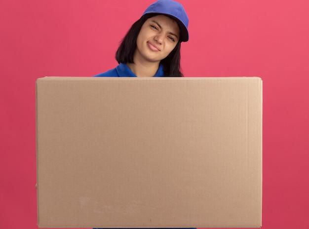 Jovem entregadora de uniforme azul e boné segurando uma grande caixa de papelão fazendo uma boca irônica com uma expressão desapontada em pé sobre a parede rosa