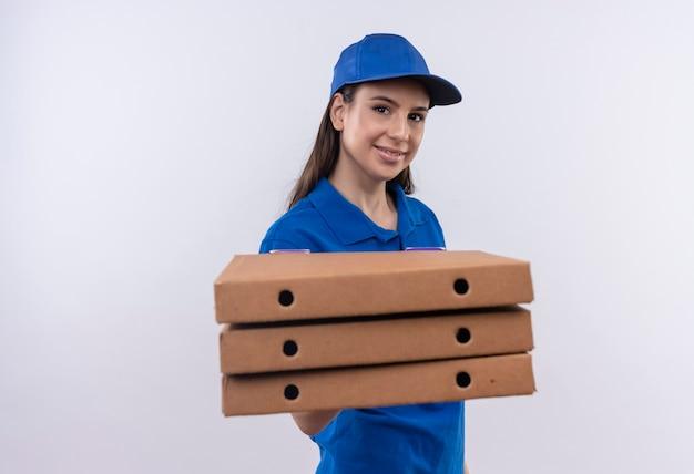 Jovem entregadora de uniforme azul e boné segurando uma pilha de caixas de pizza, olhando para a câmera com um sorriso confiante no rosto