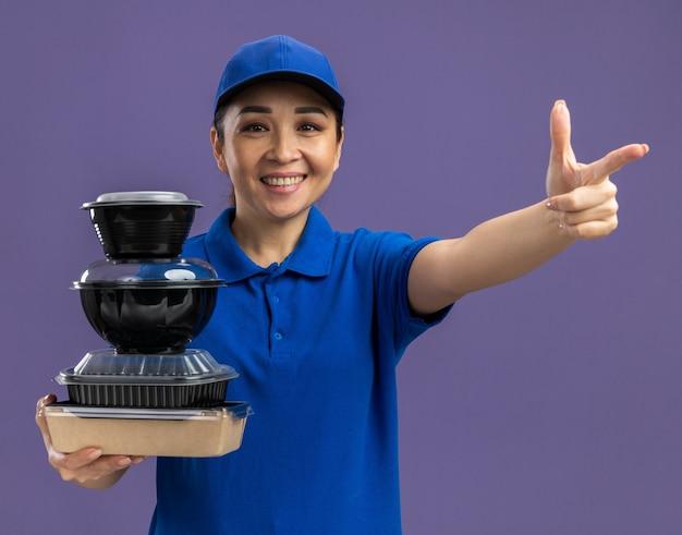 Jovem entregadora de uniforme azul e boné segurando uma pilha de pacotes de comida, sorrindo alegremente, apontando com o dedo indicador em pé sobre a parede roxa