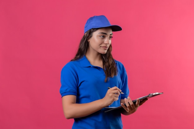 Jovem entregadora de uniforme azul e boné segurando uma prancheta com uma caneta olhando para o lado com um sorriso confiante em pé sobre o fundo rosa