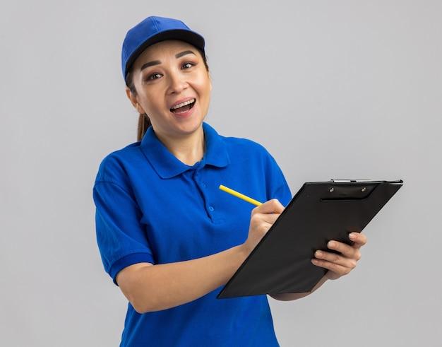 Jovem entregadora de uniforme azul e boné segurando uma prancheta e uma caneta escrevendo algo com um sorriso no rosto em pé sobre uma parede branca