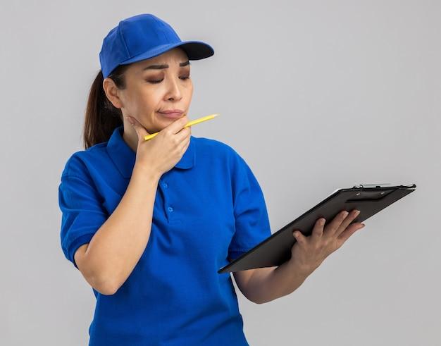 Jovem entregadora de uniforme azul e boné segurando uma prancheta e uma caneta, olhando com expressão pensativa e pensando em pé sobre uma parede branca
