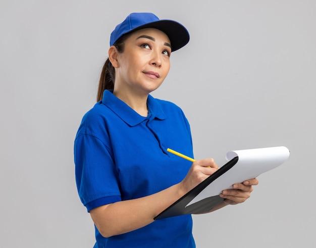 Jovem entregadora de uniforme azul e boné segurando uma prancheta e uma caneta, olhando perplexa em pé sobre uma parede branca