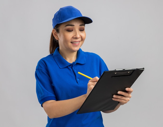 Jovem entregadora de uniforme azul e boné segurando uma prancheta e uma caneta, sorrindo confiante escrevendo algo em pé sobre uma parede branca