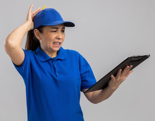Jovem entregadora de uniforme azul e boné segurando uma prancheta, olhando para ela confusa e descontente com a mão na cabeça por engano em pé sobre uma parede branca