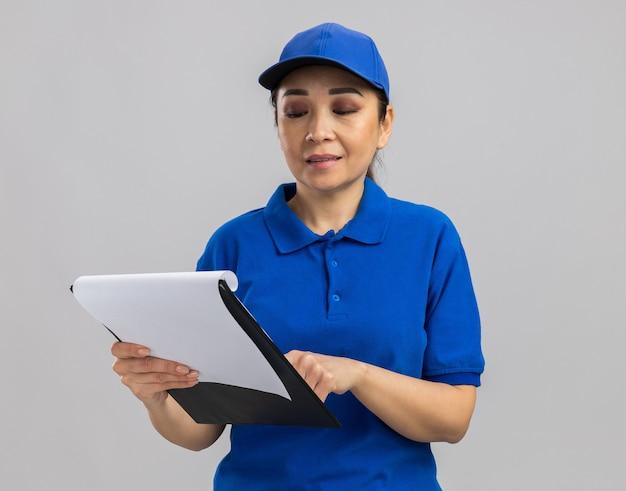 Jovem entregadora de uniforme azul e boné segurando uma prancheta, olhando para ela, sorrindo confiante em pé sobre uma parede branca