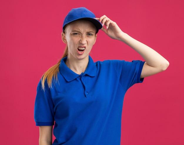 Jovem entregadora de uniforme azul e boné sendo confundida com a mão na cabeça por engano em pé sobre uma parede rosa