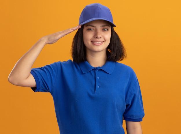Jovem entregadora de uniforme azul e boné sorridente e confiante saudando em pé sobre a parede laranja