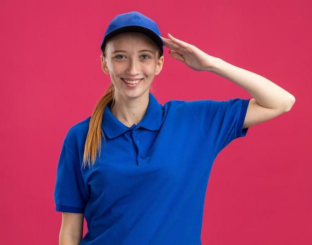 Jovem entregadora de uniforme azul e boné sorridente e confiante saudando em pé sobre a parede rosa